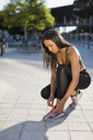 Young woman tying her shoes before workout - MAUF02149