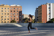 Young woman running along apartment blocks in the city - MAUF02152