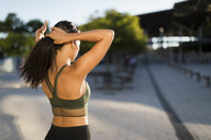 Sporty young woman doing her hair in the city - MAUF02155
