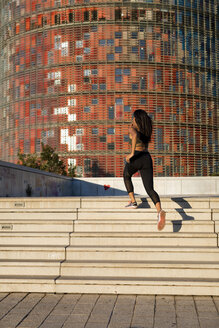 Young woman running up stairs in the city - MAUF02173