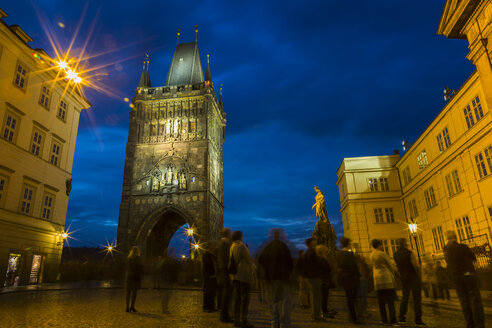 Czechia, Prague, Old Town Bridge Tower at blue hour, tourists in the foreground - JUNF01661