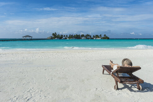 Maledives, Ari Atoll, Nalaguraidhoo, Sun Island Resort, back view of woman relaxing on the beach - RUNF00729