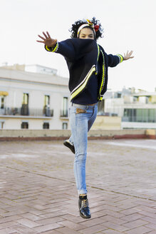 Portrait of happy young woman jumping in the city - ERRF00423