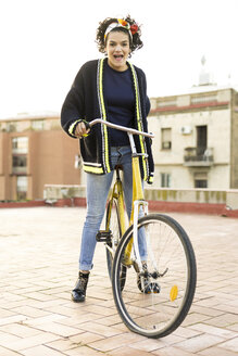 Portrait of happy young woman with bicycle in the city - ERRF00426