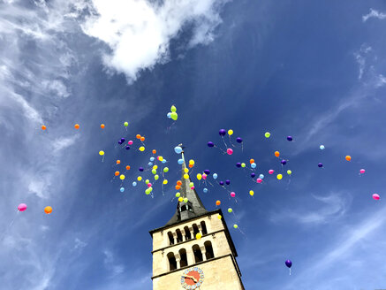 Germany, Sindelfingen, colourful wedding balloons in the sky over church spire - MABF00513