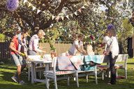 Friends preparing table at picnic in garden - ASTF00227