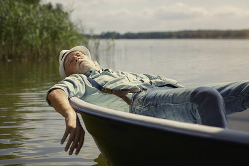 Senior man relaxing in rowing boat on a lake - VWF00019