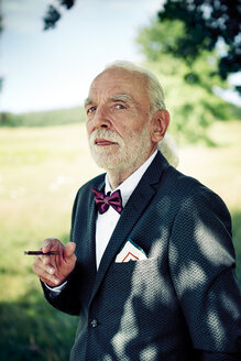 Portrait of senior man wearing suit coat, bow tie and dress handkerchief in nature smoking cigarillo - VWF00022