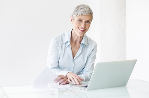 Portrait of smiling mature businesswoman working on laptop - VWF00028
