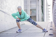 Portrait of smiling mature woman stretching in the city - VWF00031