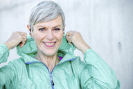 Portrait of smiling sporty mature woman with earbuds - VWF00034