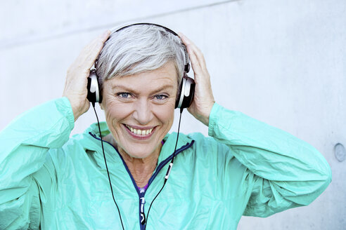 Portrait of smiling sporty mature woman with headphones - VWF00040