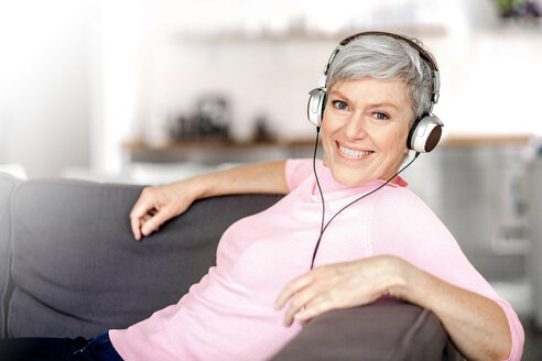 Portrait of relaxed mature woman sitting on couch listening music with headphones - VWF00043