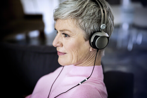 Content mature woman listening music with headphones at home - VWF00046