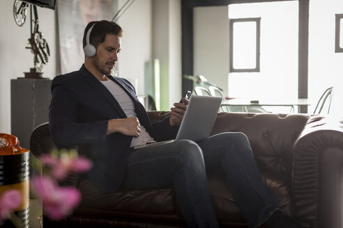 Man with headphones sitting on couch using cell phone and laptop - MAUF02180