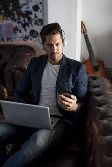 Man with headphones sitting on couch using cell phone and laptop - MAU02183