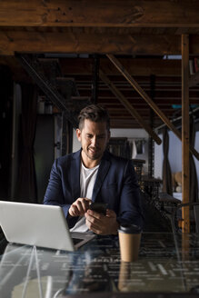 Smiling businessman using cell phone and laptop in a studio loft - MAUF02186