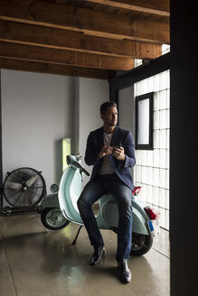 Man with motor scooter in a loft using cell phone - MAUF02189