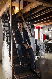 Man sitting on stairs in a studio loft - MAUF02192