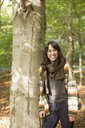 Smiling young woman leaning on tree in forest - ASTF00361