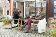 Young couple having coffee at cafe backyard - ASTF00370