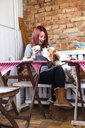 Happy young woman with Basset Hound smelling coffee at cafe table - ASTF00436