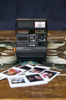 Instant camera and photographs on wooden table - ASTF00454