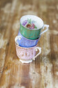 Various tea cups stacked on wooden table - ASTF00457