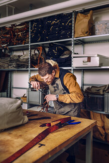 Male worker holding ruler while making bag at worktable in factory - ASTF00469