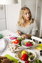 Young woman looking away while cutting vegetables in kitchen - ASTF00517