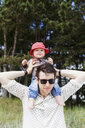 Baby boy sitting on father's shoulder outdoors - ASTF00607