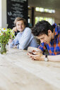 Man looking at friend using smart phone while sitting at cafe table - ASTF00670