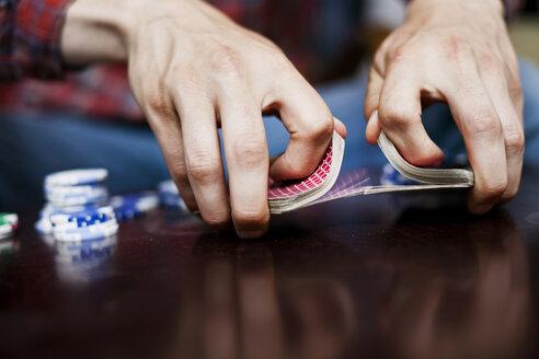 Cropped image of man's hands mixing and shuffling deck of cards - ASTF00781