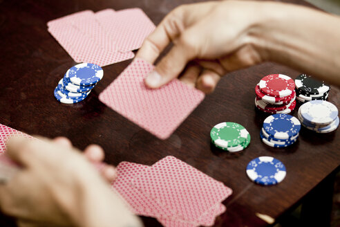 Cropped image of man's hands playing cards at home - ASTF00787
