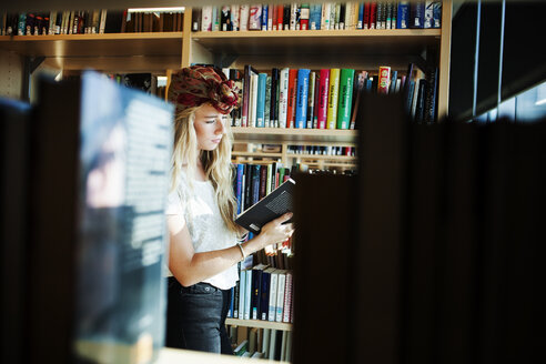 Young college student reading book in library - ASTF00868