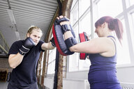 Young man with female trainer practicing boxing in health club - ASTF00892