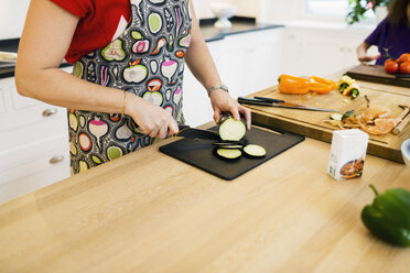 Midsection of mother chopping egg plant in kitchen - ASTF00934