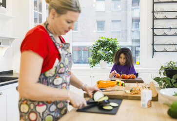 Mother and daughter chopping vegetables in kitchen - ASTF00937