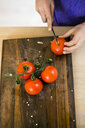 Cropped image of girl slicing tomatoes on cutting board in kitchen - ASTF00940
