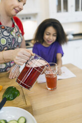 Mother serving glass of juice to daughter in kitchen - ASTF00949