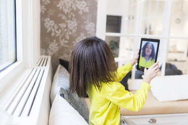 Side view of little girl taking selfie through digital tablet while sitting in living room - ASTF00955