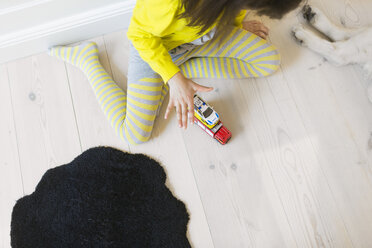 High angle view of girl playing with toy cars on hardwood floor - ASTF00958