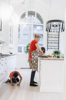 Boy playing with toy car while mother and daughter cooking food in kitchen - ASTF00961