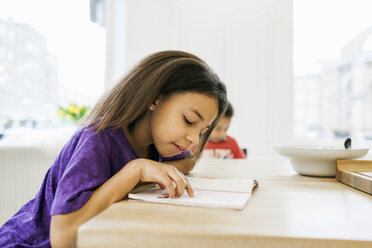 Side view of girl reading book with brother in background at kitchen - ASTF00964