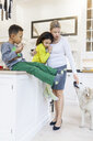 Full length of family with dog in kitchen - ASTF00970