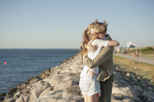 Loving couple embracing on rocky shore at beach - ASTF01135