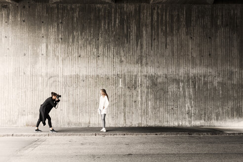 Woman photographing friend on sidewalk against wall - ASTF01192