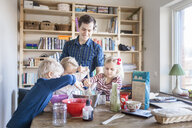 Happy father looking at children mixing ingredients at home - ASTF01258