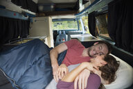 Affectionate couple cuddling in the back of camper van - HEROF03599