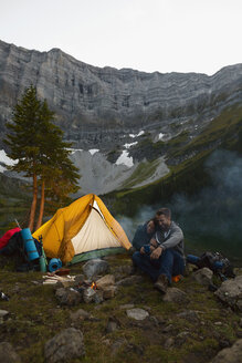 Affectionate couple cuddling at campfire at remote mountain lakeside campsite - HEROF03602